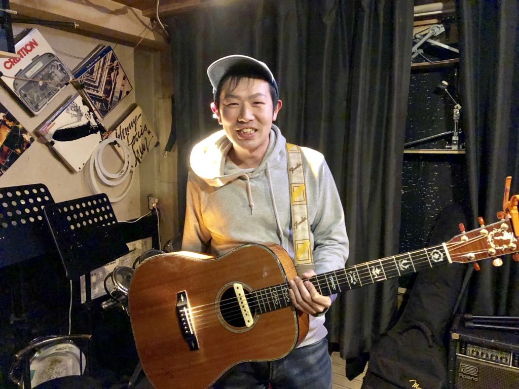 斉藤省悟さんがギターを持っている写真
