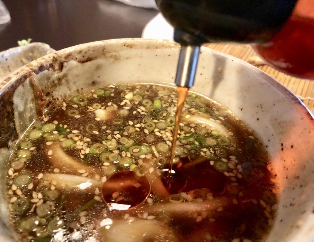 うどんスープにラー油を入れているシーン