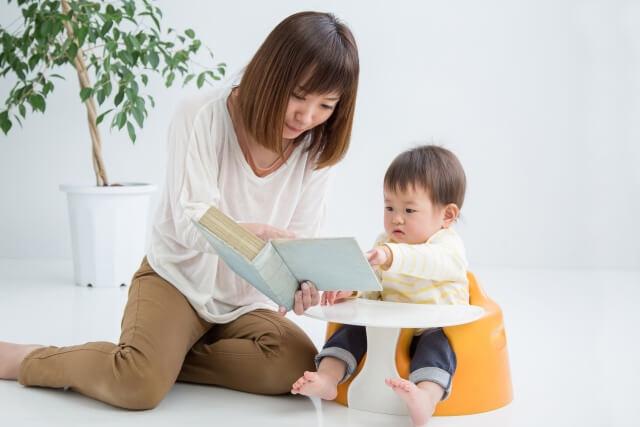 子どもにお母さんが絵本を読んであげる様子